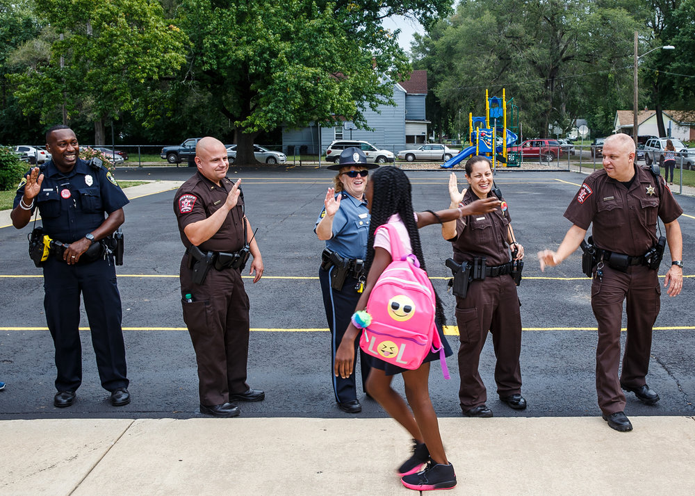 Members of the Springfield Police & Fire Departments, Sangamon County Sheriffs Office, Department of Corrections and the Capitol Police lined up to give high fives and hugs to kids as they arrive for the first day of school for Dist. 186. students at Feitshans Elementary School, Monday, Aug. 21, 2017, in Springfield, Ill. Court Security Officer Rhonda Kopietz, of the Sangamon County Sheriffs Dept., adopted a kindergarten class last year and helped organize an effort for an officer to adopt each kindergarten class in the school. [Justin L. Fowler/The State Journal-Register]