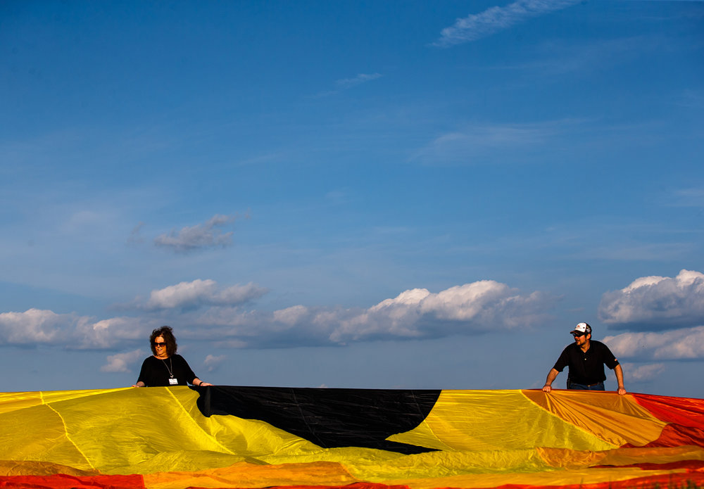 "Ann Siltman, left, and Jason McMillin, right, help pull out the hot air balloon ""Auspicious"" prior to a flight after a ribbon cutting ceremony for the Lincoln Balloon Festival at the Logan County Airport, Thursday, Aug. 24, 2017, in Lincoln, Ill. [Justin L. Fowler/The State Journal-Register]"