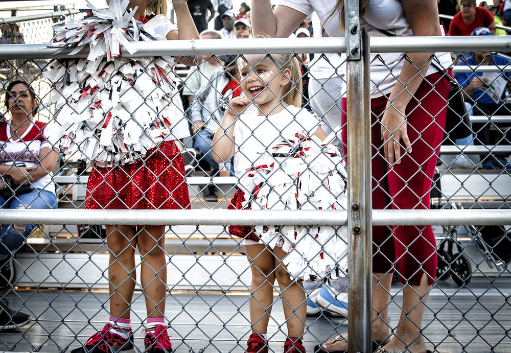 Charlotte Jarmer, 4, center, waves towards her sister, Chloe, a Springfield High School cheerleader, prior to kickoff between Springfield and Normal U-High for the first week of high school football at Memorial Stadium, Friday, Aug. 25, 2017, in Springfield, Ill. [Justin L. Fowler/The State Journal-Register]
