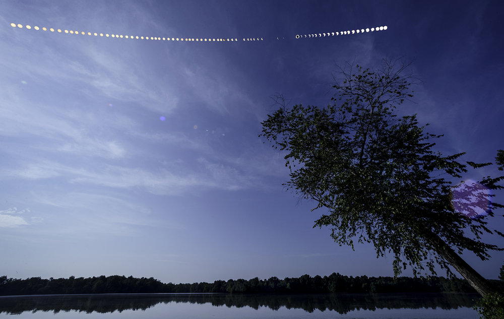 A composite image shows the path of the sun exposed every four minutes during the total solar eclipse over the Carbondale Reservoir Monday, Aug. 21, 2017. Gaps in the sequence are where clouds obscured the sun. [Ted Schurter/The State Journal-Register]