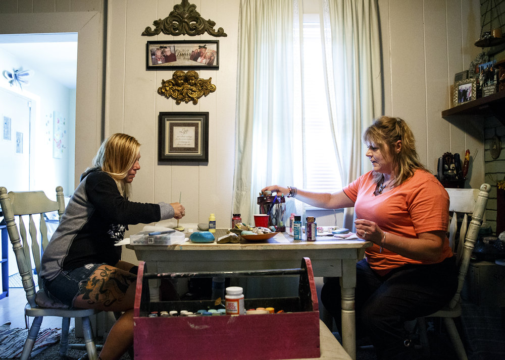 "Dee Dee Beard, left, and Misty Mitchell paint rocks at Mitchell's home Thursday, Aug. 24, 2017. ""If we can just put a little bit of kindness and happiness out there, it don't hurt,"" Mitchell says. [Rich Saal/The State Journal-Register]"