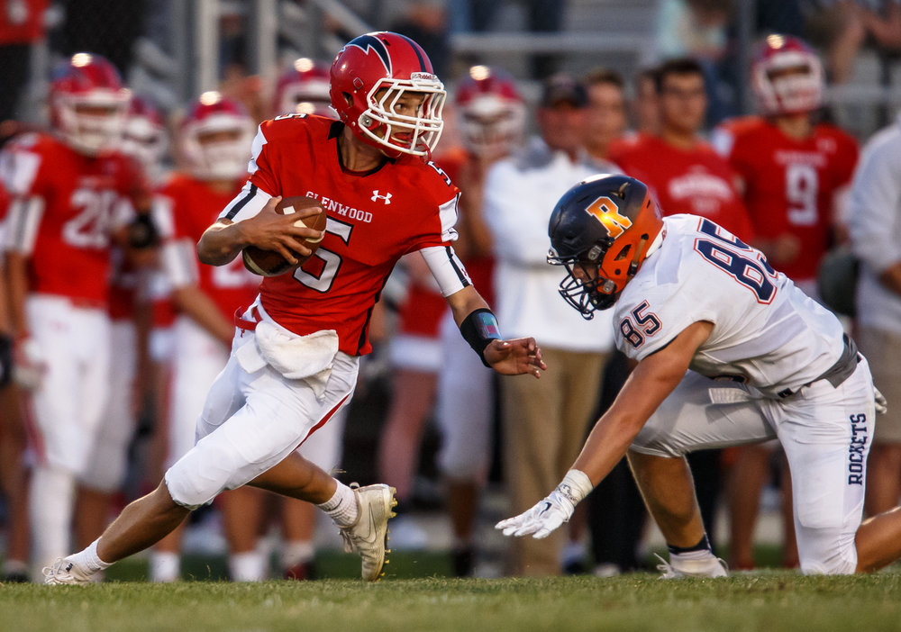 Glenwood's Luke Lehnen (5) escapes the grasp of Rochester's Mike McNicholas (85) as he scrambles out of the pocket in the first quarter at Glenwood High School, Friday, Sept. 1, 2017, in Chatham, Ill. [Justin L. Fowler/The State Journal-Register]
