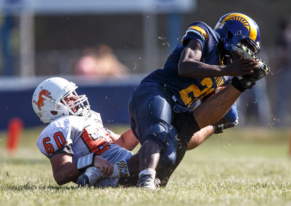 Lanphier's Brayan Reyes (60) drags down Southeast's Vincent Hill (21) on a rush in the third quarter at Southeast High School, Saturday, Sept. 2, 2017, in Springfield, Ill. [Justin L. Fowler/The State Journal-Register]
