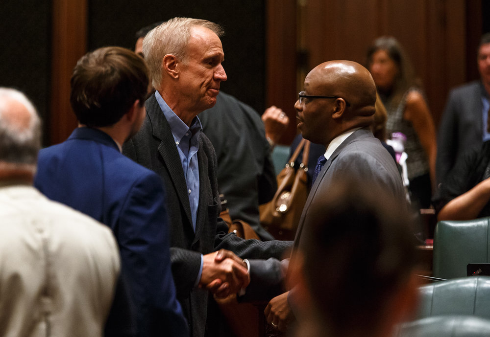 Illinois Governor Bruce Rauner shakes hands with Illinois State Rep. Will Davis, D-Homewood, on the floor of the Illinois House after the education funding bill Davis sponsored passed on the second attempt with a vote of 73-34-3 during a special session at the Illinois State Capitol, Monday, Aug. 28, 2017, in Springfield, Ill. [Justin L. Fowler/The State Journal-Register]