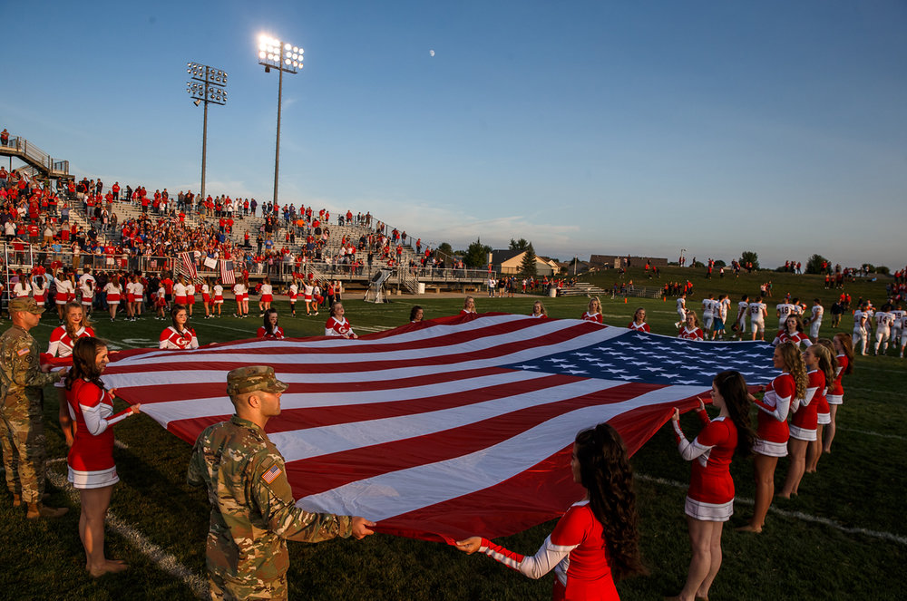 The Glenwood cheerleaders stretch out a large American Flag at midfield as the Titans get set to take on Rochester at Glenwood High School, Friday, Sept. 1, 2017, in Chatham, Ill. [Justin L. Fowler/The State Journal-Register]