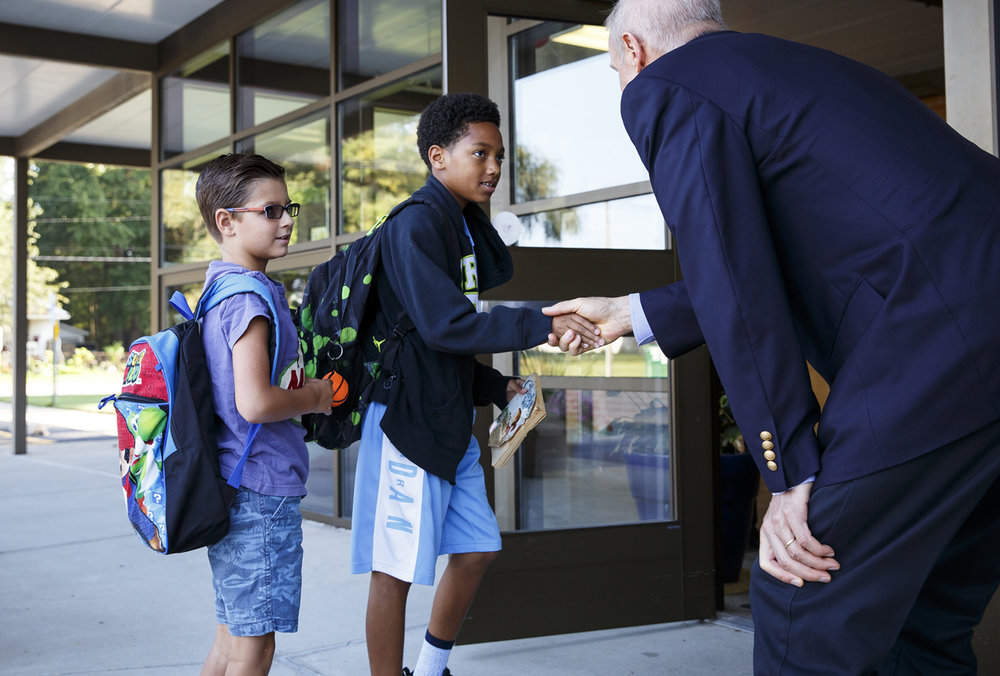 Broden Duecker, left, and Rakim Higgerson, say helllo to Gov. Bruce Rauner who greeted arriving students at Ball Charter School Wednesday, Aug. 30, 2017. Rauner and a group of downstate legislators were at the school to talk to students about the school funding reform bill passed a day earlier by the Senate. [Rich Saal/The State Journal-Register]