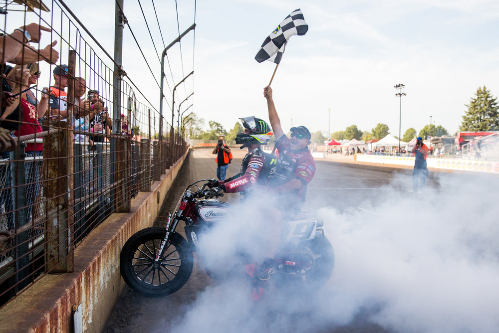 Crew Cheif Kenny Tolbert waves the checkered flag as Jared Mees does a burnout on his Indian Scout FTR750 after winning the AMA Harley-Davidson Springfield Mile II at the Illinois State Fairgrounds, Sunday, Sept. 3, 2017, in Springfield, Ill. [Justin L. Fowler/The State Journal-Register]