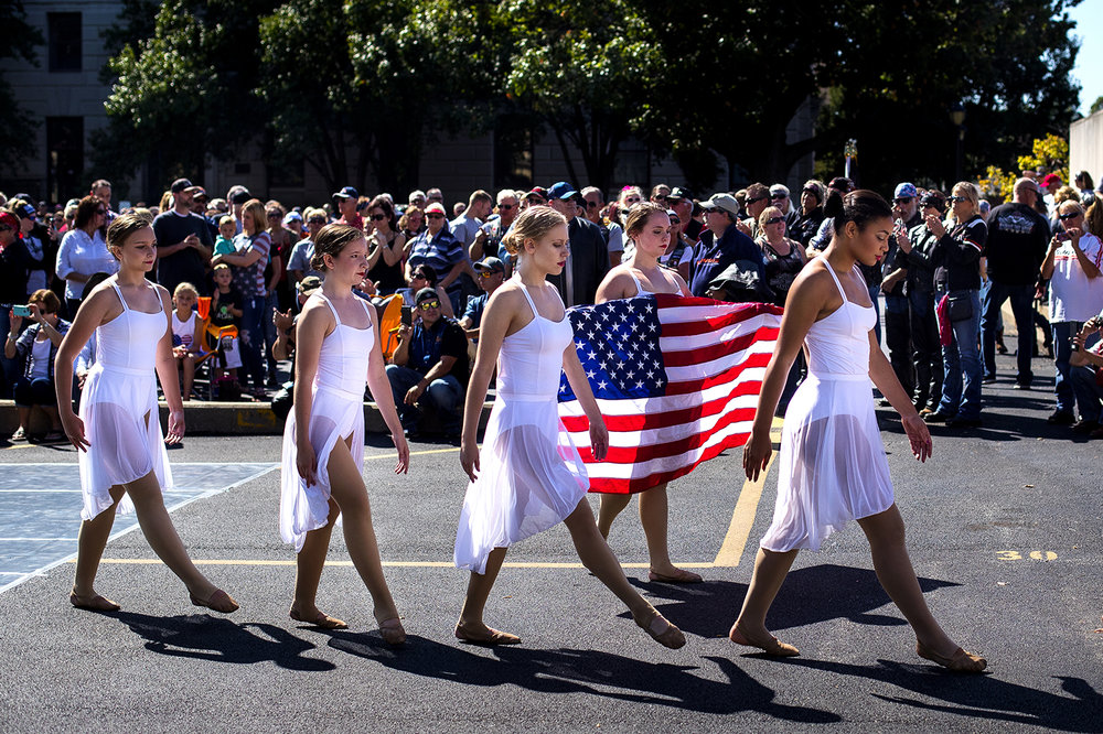 Natalie Enlow carries the U.S. flag after members of Dance Creations Dance Studio performed during the Ride To Remember 9-11 Annual Memorial Parade & Ceremony on the Capitol grounds Sunday, Sept. 10, 2017. [Ted Schurter/The State Journal-Register]