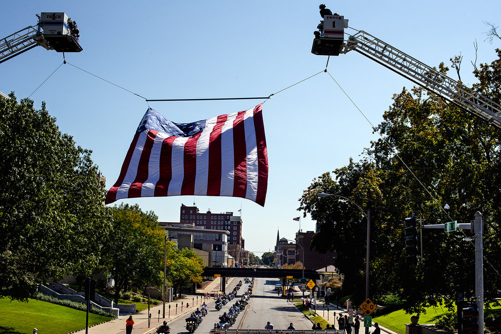 Motorcycle riders make their way past a giant U.S. flag suspended between two ladder trucks on Second Street during the Ride To Remember 9-11 Annual Memorial Parade & Ceremony Sunday, Sept. 10, 2017. [Ted Schurter/The State Journal-Register]