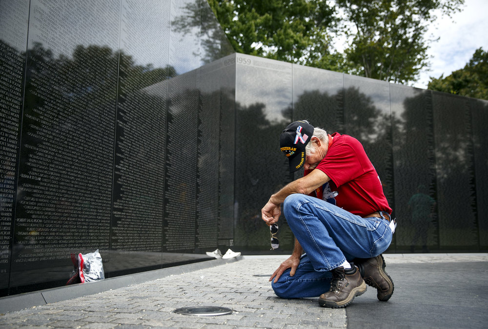 Frank Burch pauses at the Vietnam War Veterans Memorial in front of the names of soldiers that he served with. Burch served as a machine gunner with the Marines Corps and is a graduate of Lanphier High School.