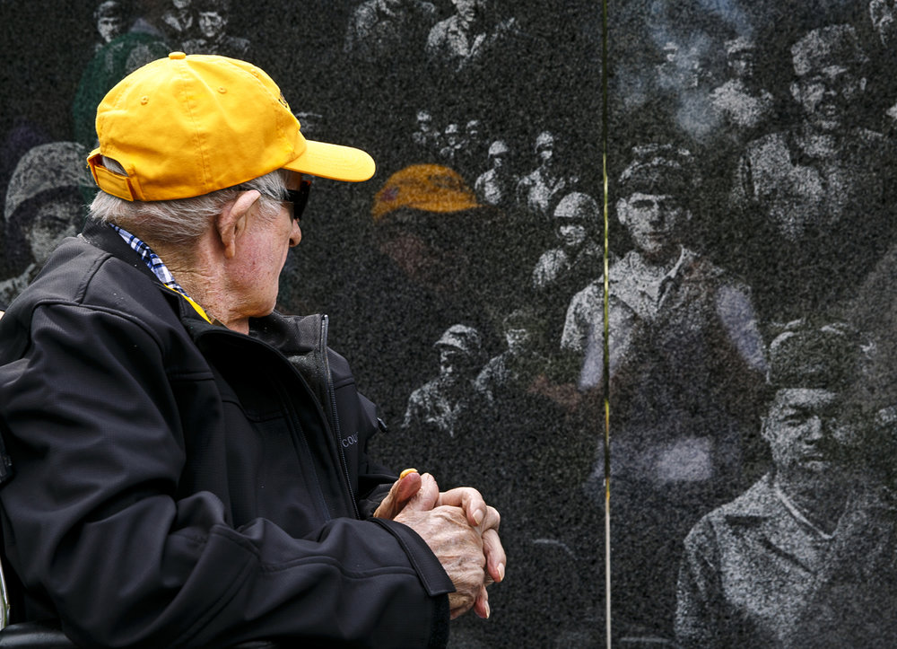 Robert Ackerson passes etchings that represent the Army, Navy, Air Force, Marines and Coast Guard on a black granite wall at the Korean War Veterans Memorial. Ackerson is a U.S. Army veteran of the war and Bronze Star recipient.