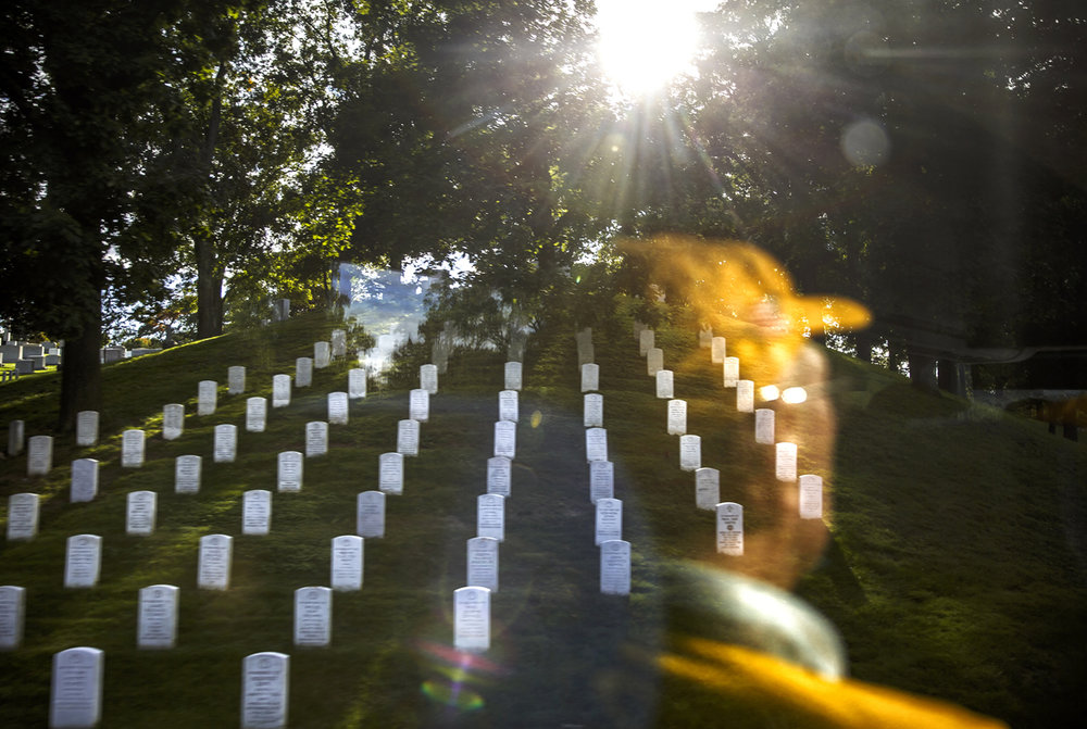 Stones on a hillside mark the graves of Missing in Action, viewed from a bus window as it carries members of the Honor Flight into Arlington National Cemetery.
