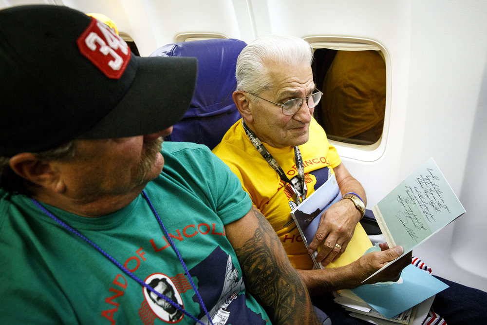 Arnold Grube reads one of the cards he received during mail call on the flight back to Springfield. The delivery of cards and letters from home was organized by the Land of Lincoln Honor Flight to replicate the mail call that was such an important connection for the soldiers during their service.