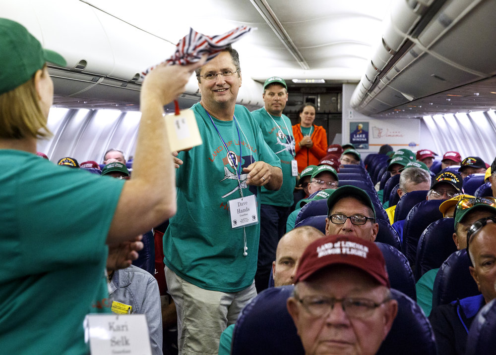 Mail packets are passed to veterans on the flight home from Washington.