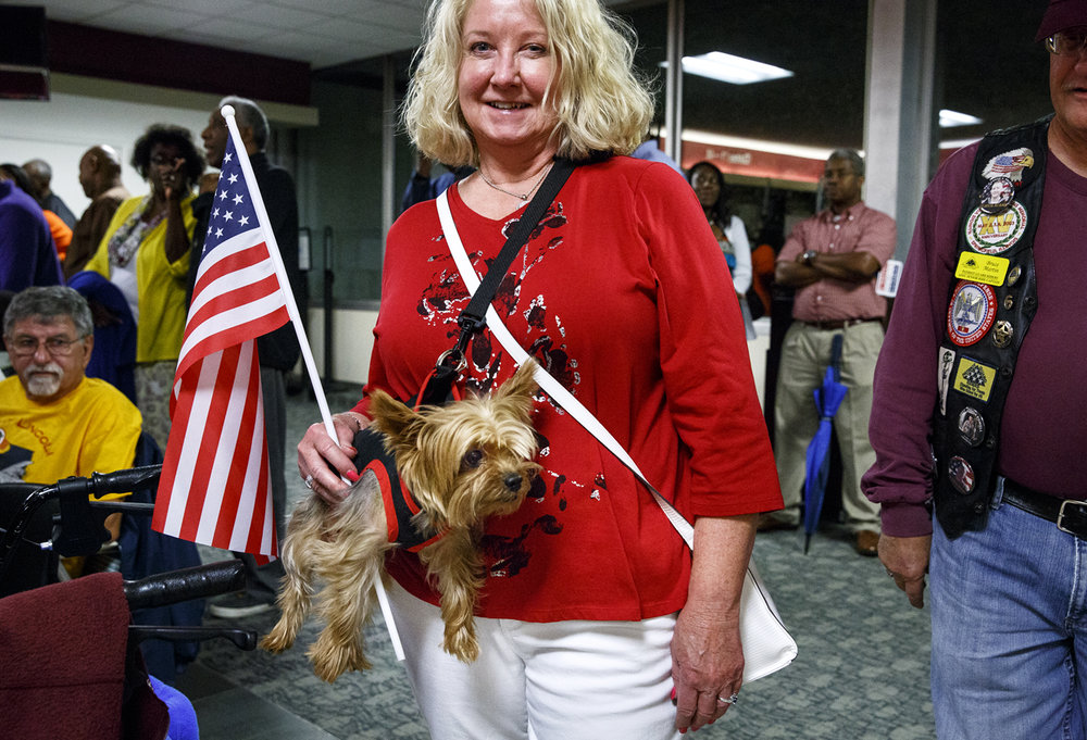 Gloria Deatherage and her Yorkie, Bentley, wait with others at Springfield's Capital Airport for the return of the Land of Lincoln Honor Flight Tuesday, Sept. 12, 2017. Deatherage's friend Johnny Adelman was a guardian for Ray Bolinski, a World War II veteran on the flight. [Rich Saal/The State Journal-Register]