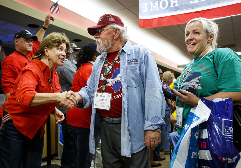 A woman reaches out to thank Mike Parkhill for his military service after he returned to Springfield on the Land of Lincoln Honor Flight. Parkhill is a U.S. Army veteran of the Vietnam War and was accompanied on the flight by his daughter, Amy Summers, right.
