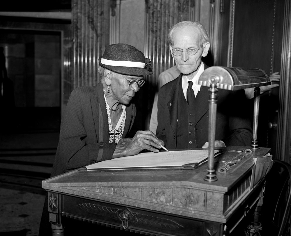 Fay watches Adeline Jenkins, 99, signs the tomb guest register, Sept. 21, 1947. Jenkins had been at the tomb to attend an observance of the 84th anniversary of the signing by Lincoln of the Emancipation Proclamation.  The State Journal-Register/archive