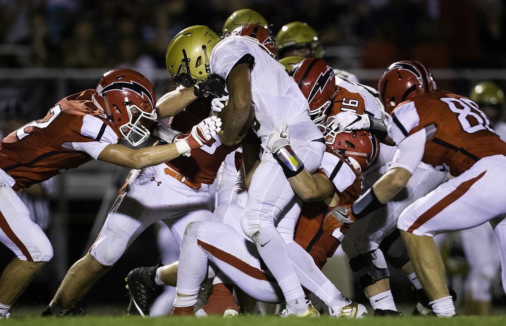 The Glenwood Titans wrap up Sacred Heart-Griffin's Spencer Redd at Glenwood High School Friday, Sept. 15, 2017. [Ted Schurter/The State Journal-Register]