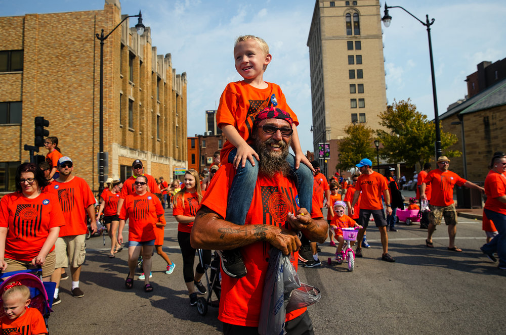Brysinn Phillipps rides on his grandfather Dean Phillipps' shoulders as they march with the  Laborers' International Union of North America Local 477 during the Labor Day Parade in downtown Springfield Monday, Sept. 4, 2017. [Ted Schurter/The State Journal-Register]