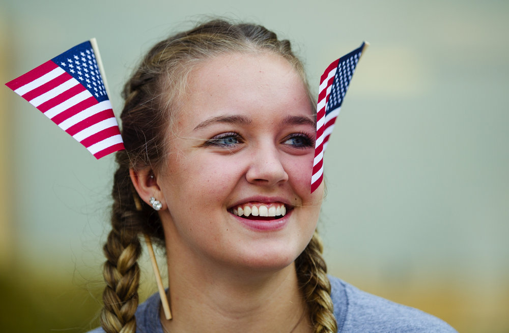 Cati West wears two U.S. flags in her hair as she watches the Labor Day Parade in downtown Springfield Monday, Sept. 4, 2017. [Ted Schurter/The State Journal-Register]