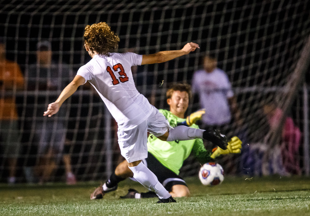 Springfield's Kelby Phillips (13) sends a shot past Glenwood's Collin Cramer (0) for his third goal of the game and the golden goal as the Senators defeat Glenwood 3-2 in overtime at Lee Field, Tuesday, Sept. 19, 2017, in Springfield, Ill. [Justin L. Fowler/The State Journal-Register]