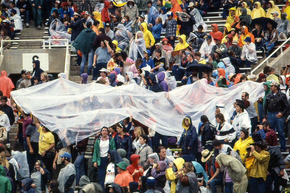 Fans pull plastic sheeting over themselves in an attempt to keep dry at the Farm Aid concert at Memorial Stadium in Champaign, Ill. Sept. 22, 1985. [File/The State Journal-Register]