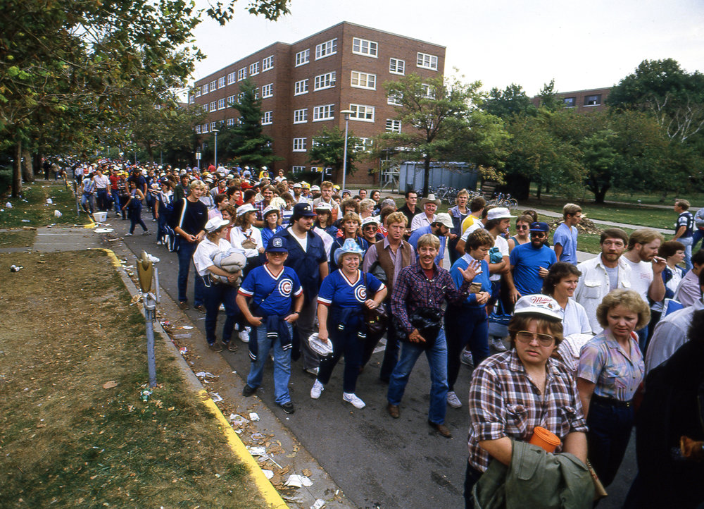 A crowd on their way to the Farm Aid concert at Memorial Stadium fills a street on the University of Illinois campus in Champaign, Ill. Sept. 22, 1985. [File/The State Journal-Register]