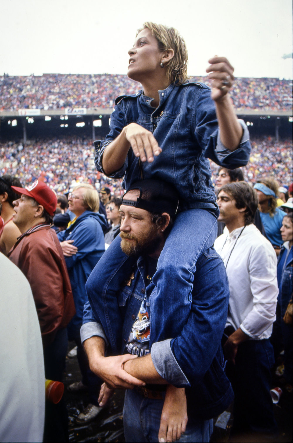A woman gets a better view sitting on the shoulders of a friend at the Farm Aid concert at Memorial Stadium in Champaign, Ill. Sept. 22, 1985. [File/The State Journal-Register]