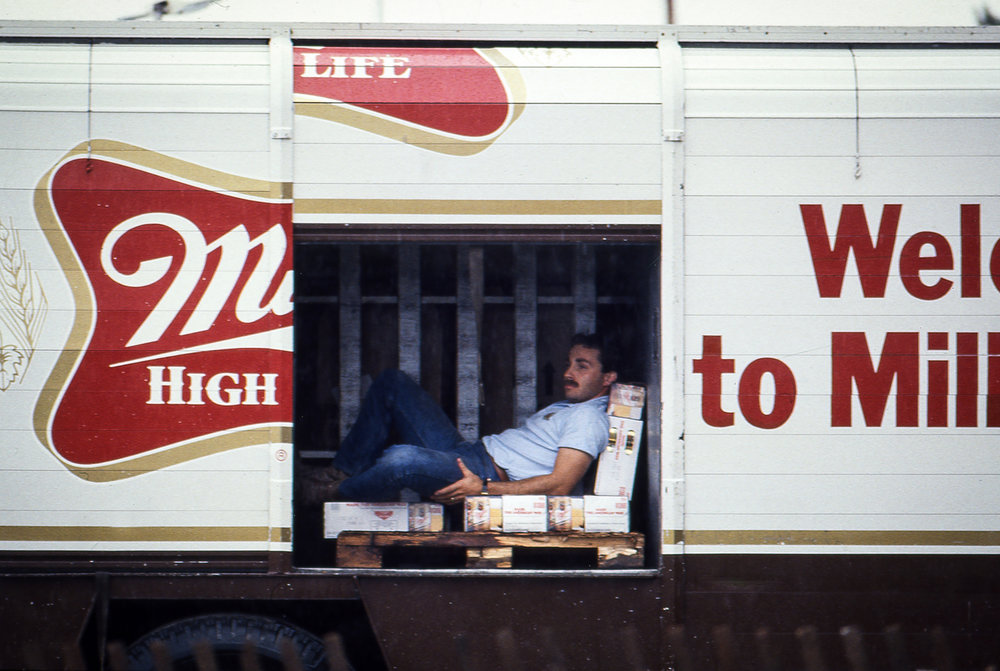 A beer truck driver found shelter from the rain during the Farm Aid concert at Memorial Stadium in Champaign, Ill. Sept. 22, 1985. [File/The State Journal-Register]