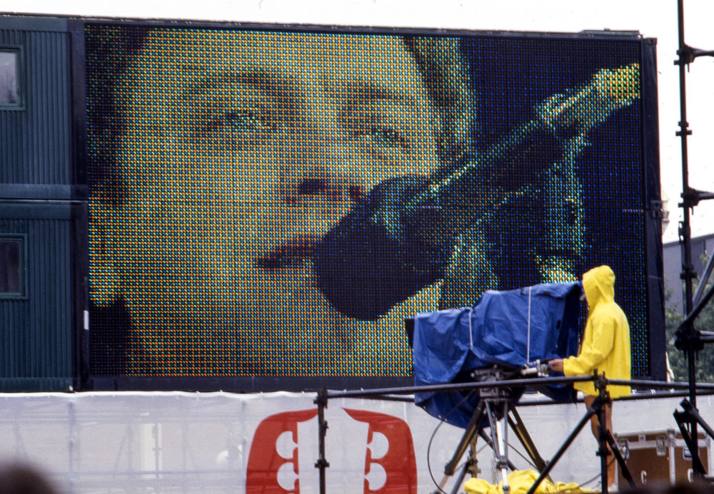 Lou Gramm, lead singer of the group Foreigner, is seen on a jumbo screet at the Farm Aid concert at Memorial Stadium in Champaign, Ill. Sept. 22, 1985. [File/The State Journal-Register]