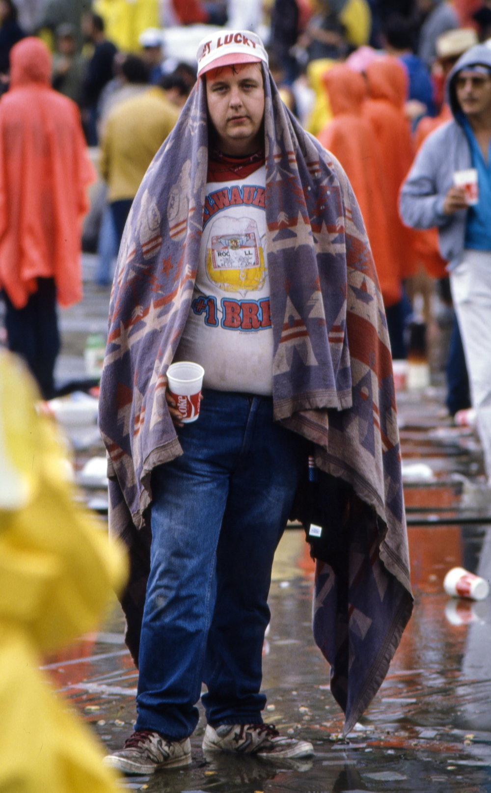 A spectator uses a blanket for rain protection during the Farm Aid concert at Memorial Stadium in Champaign, Ill. Sept. 22, 1985. [File/The State Journal-Register]