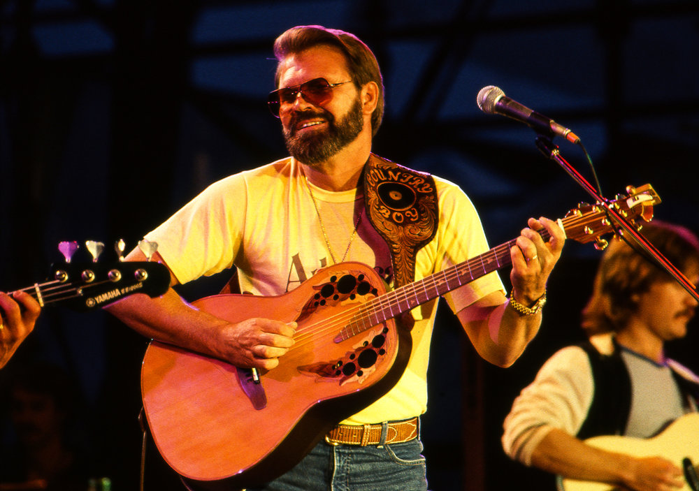 "Glen Campbell delivered four of his classic hits, ""Galveston,"" ""By the Time I Get to Phoenix,"" ""Wichita Lineman,"" and ""Rhinestone Cowboy"" at the Farm Aid concert at Memorial Stadium in Champaign, Ill. Sept. 22, 1985. [File/The State Journal-Register]"