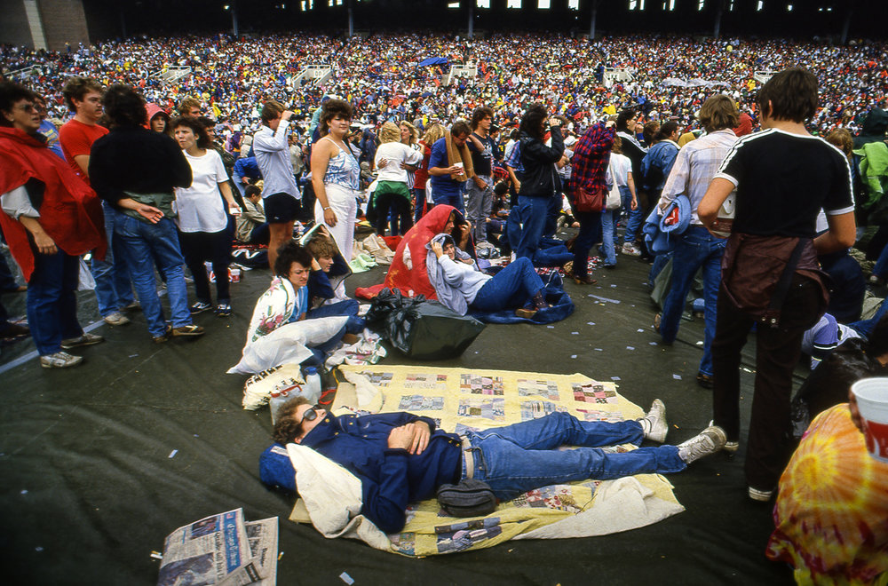 Amidst the crowd at Memorial Stadium, some fans found room to stretch out between shows at the Farm Aid concert in Champaign, Ill. Sept. 22, 1985. [File/The State Journal-Register]
