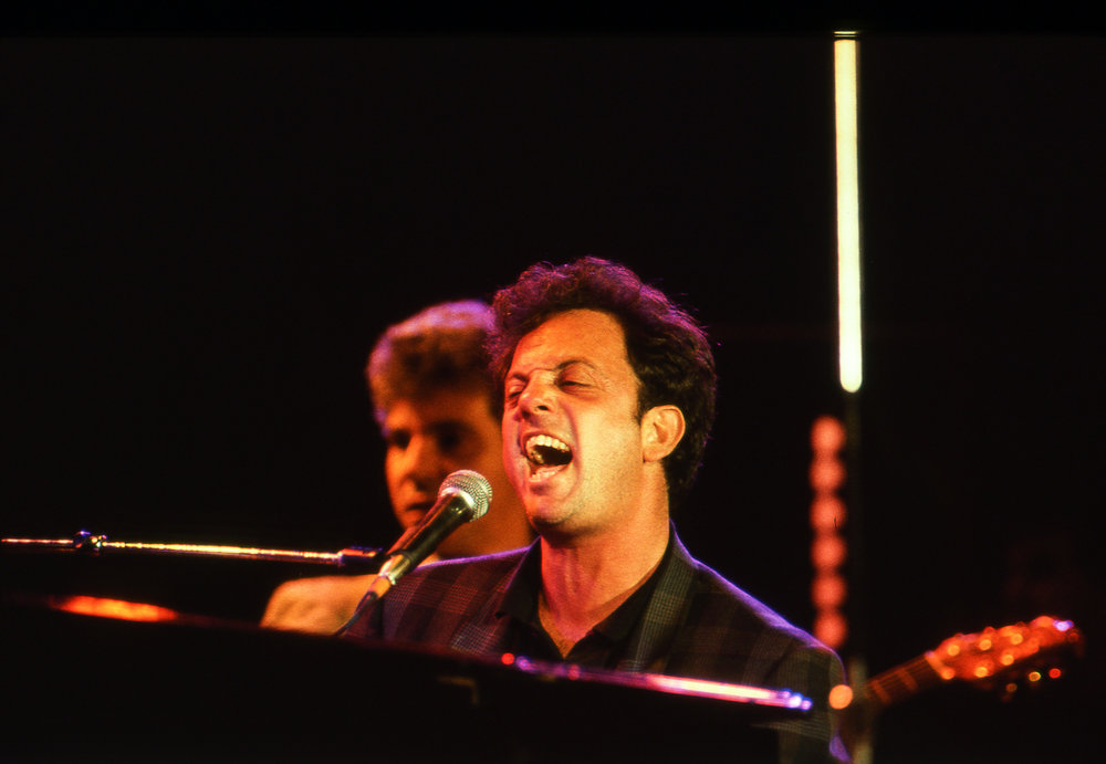 "Billy Joel performs ""Only the Good Die Young"" at the Farm Aid concert at Memorial Stadium in Champaign, Ill. Sept. 22, 1985. [File/The State Journal-Register]"