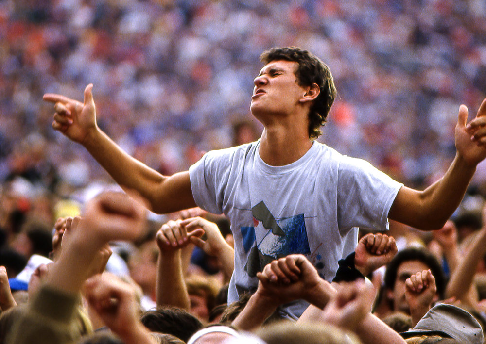 A fan gets into the music at the Farm Aid concert at Memorial Stadium in Champaign, Ill. Sept. 22, 1985. [File/The State Journal-Register]