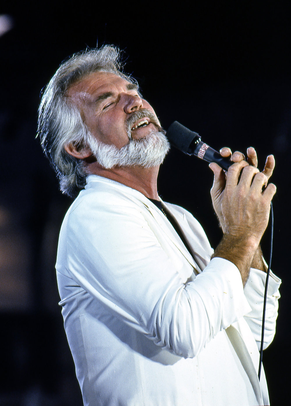Kenny Rogers in a familiar pose during his performance at the Farm Aid concert at Memorial Stadium in Champaign, Ill. Sept. 22, 1985. [File/The State Journal-Register]