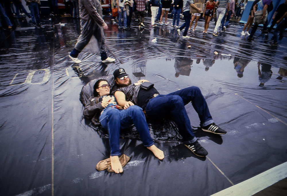 Two fans seem oblivious to the water around them during the Farm Aid concert at Memorial Stadium in Champaign, Ill. Sept. 22, 1985. [File/The State Journal-Register]