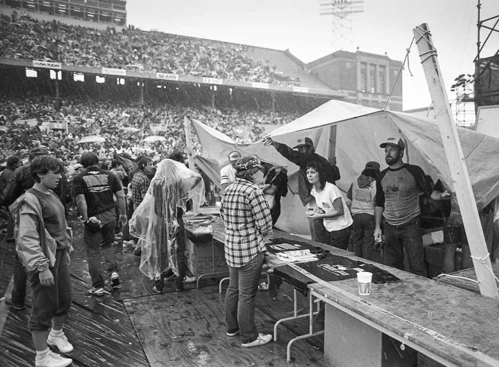 T-shirts, but no rain coats, were sold at a stand in Memorial Stadium during the Farm Aid concert at Memorial Stadium in Champaign, Ill. Sept. 22, 1985. [File/The State Journal-Register]