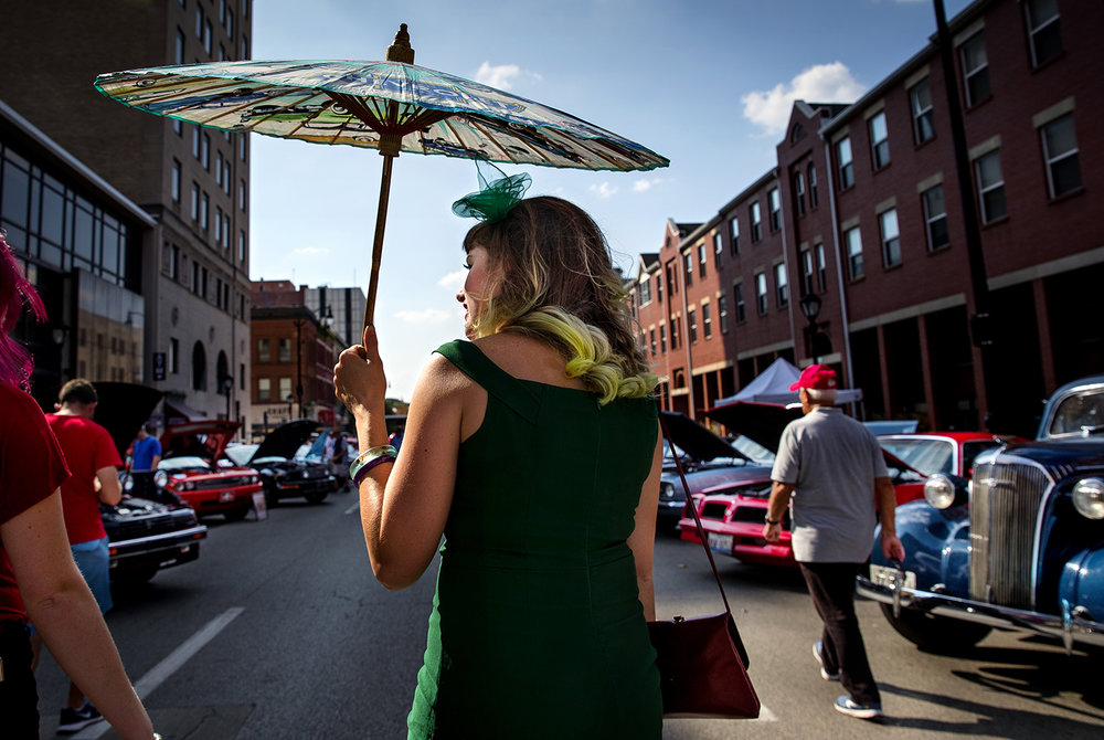 Allison Bell of Petersburg uses an umbrella to stay cool as she peruses the cars on display in a vintage outfit at the International Route 66 Mother Road Festival in downtown Springfield Saturday, Sept. 23, 2017. [Ted Schurter/The State Journal-Register]
