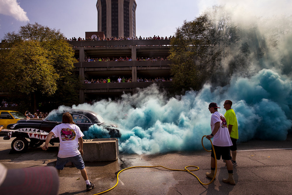 Blue smoke billows from the tires of a hot rod during the Burnout contest at the International Route 66 Mother Road Festival in downtown Springfield Saturday, Sept. 23, 2017. The blue smoke is the result of specialty tires that produce unique colors. [Ted Schurter/The State Journal-Register]