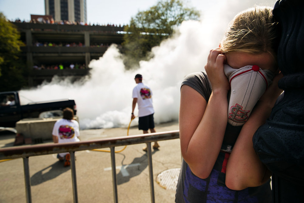 Kaylee Brasier hides her face from the sound and the smell of the Burnout contest during the International Route 66 Mother Road Festival in downtown Springfield Saturday, Sept. 23, 2017. [Ted Schurter/The State Journal-Register]