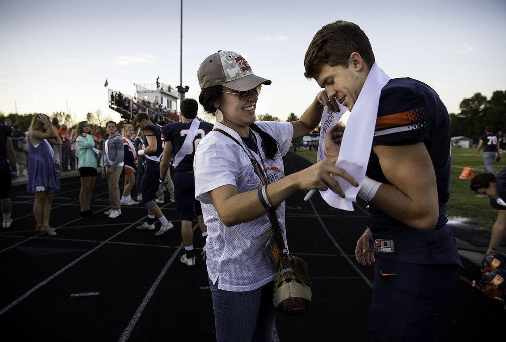 Michele Tungett helps Cade Eddington into his homecoming sash before kickoff at Rochester High School Friday, Sept. 29, 2017. [Ted Schurter/The State Journal-Register]