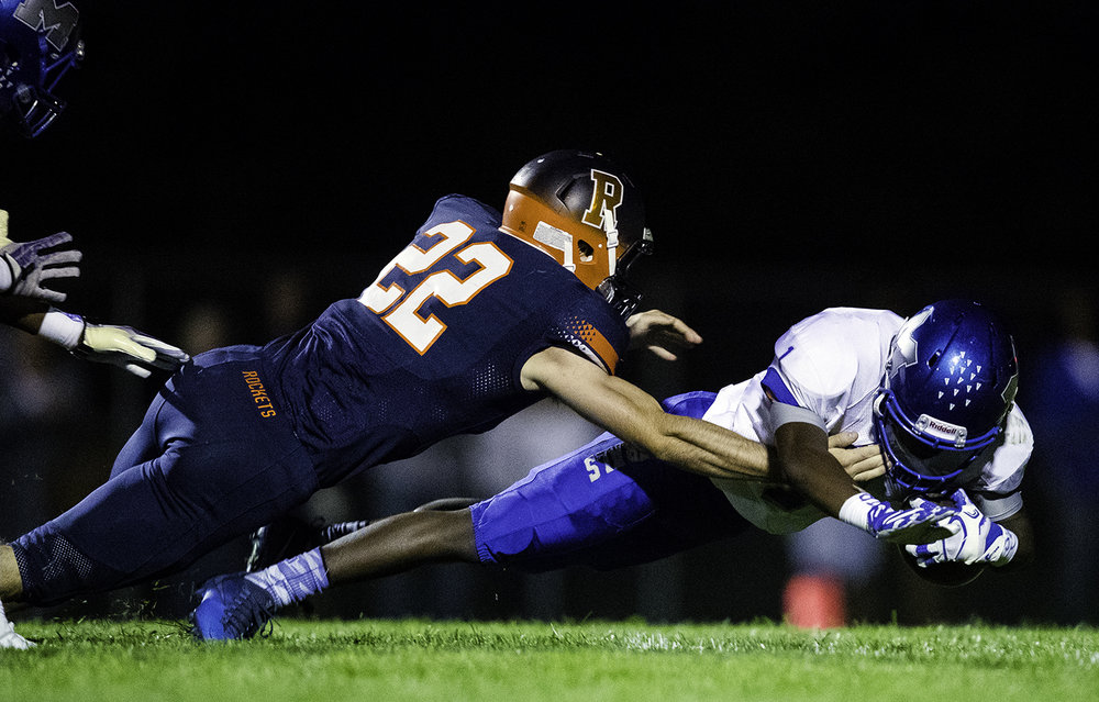 Rochester's Brandon Morris dives for Decatur MacArthur's Martiece O'Neal on a punt return at Rochester High School Friday, Sept. 29, 2017. [Ted Schurter/The State Journal-Register]