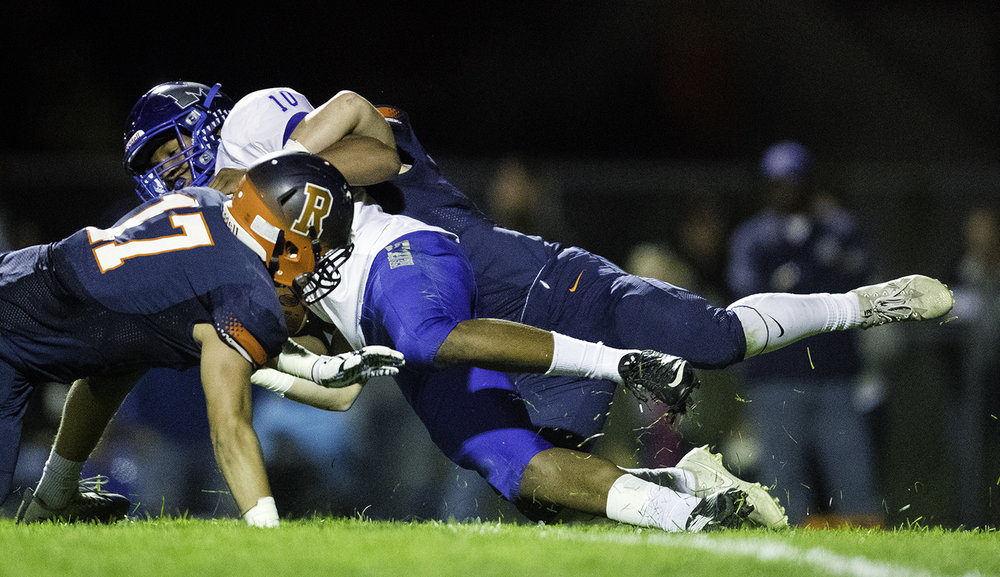 Rochester's Skylor Caruso brings down Decatur MacArthur's Ray Neal at Rochester High School Friday, Sept. 29, 2017. [Ted Schurter/The State Journal-Register]