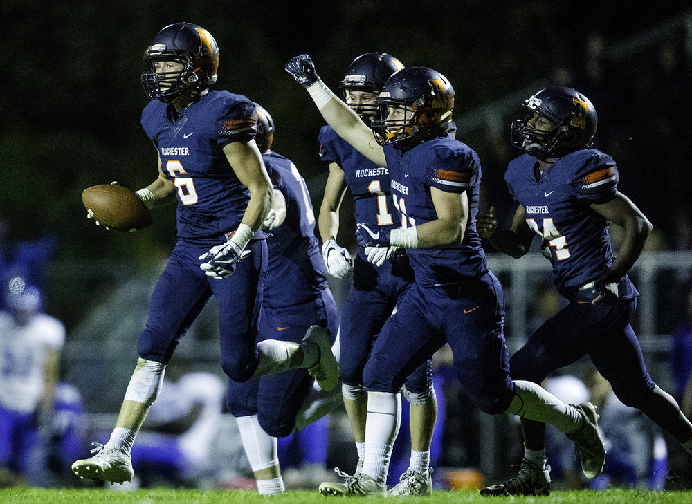 Rochester's Cade Edgington leads the Rockets back to the bench after forcing and then recovering a Decatur MacArthur fumble at Rochester High School Friday, Sept. 29, 2017. [Ted Schurter/The State Journal-Register]