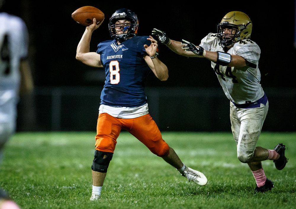 Rochester quarterback Nic Baker (8) fires off a touchdown pass under pressure from ]Sacred Heart-Griffin's John Keen (44) in the third quarter at Rocket Booster Stadium, Friday, Oct. 6, 2017, in Rochester, Ill. [Justin L. Fowler/The State Journal-Register]