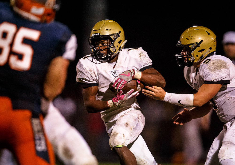Sacred Heart-Griffin's Brian Adams (1) takes the handoff from Sacred Heart-Griffin's Sam Sweetland (9) on a rush against Rochester in the third quarter at Rocket Booster Stadium, Friday, Oct. 6, 2017, in Rochester, Ill. [Justin L. Fowler/The State Journal-Register]