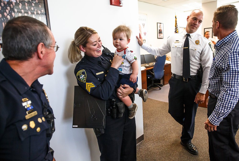 Sgt. Rikki Castles, center, of the Springfield Police Dept.,  visits with her nephew, Leo Warren, 1, who is mesmerized by his grandfather Sgt. Gerri Castles, left, as he makes funny faces after a promotion ceremony where Rikki Castles was promoted to Sergeant at Municipal Center East, Thursday, Oct. 5, 2017, in Springfield, Ill. Sgt. Rikki Castles and Sgt. Gerri Castles are the first and only father and daughter officers on the Springfield Police Department.  [Justin L. Fowler/The State Journal-Register]