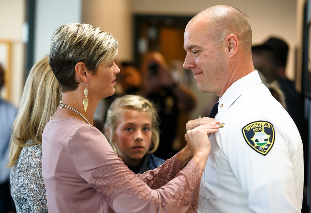 Springfield Police Department's Ken Scarlette is pinned by his wife Tracy Scarlette, as he is promoted to Deputy Chief during a promotion ceremony at Municipal Center East, Thursday, Oct. 5, 2017, in Springfield, Ill. [Justin L. Fowler/The State Journal-Register]