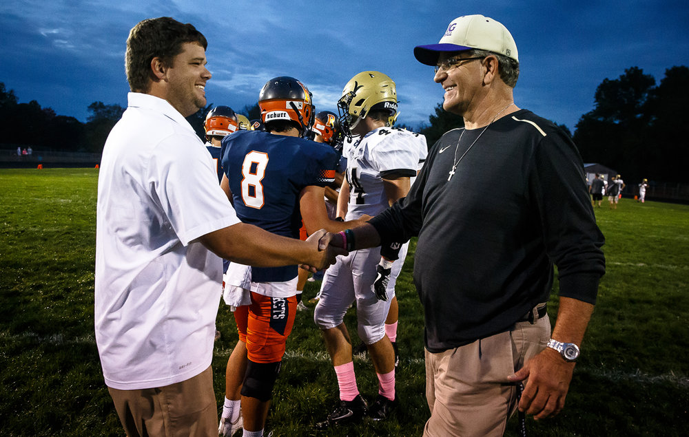 Rochester football head coach Derek Leonard shakes hands with his father, Sacred Heart-Griffin head football coach Ken Leonard, at midfield prior to the Rockets taking on the Cyclones at Rocket Booster Stadium, Friday, Oct. 6, 2017, in Rochester, Ill. [Justin L. Fowler/The State Journal-Register]